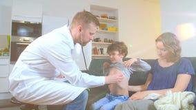 Medico domestico è venuto al ragazzo malato ed a sua madre esamina un bambino e registra le letture in taccuino stock footage