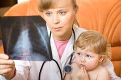 Medico e bambino che esaminano i raggi X Fotografie Stock Libere da Diritti