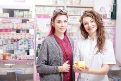 Medico e cliente davanti allo scrittorio della farmacia immagine stock libera da diritti