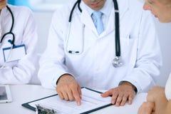 Medico e conversazione paziente mentre sedendosi allo scrittorio in ufficio Medico che indica nella forma di anamnesi Medicin fotografia stock