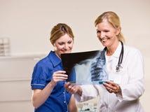 Medico e donna che esaminano raggi X Fotografie Stock Libere da Diritti