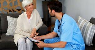 Medico e donna senior che discutono sopra la lavagna per appunti video d archivio