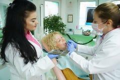 Medico e l'infermiere preparano il paziente femminile per la procedura dentaria fotografie stock