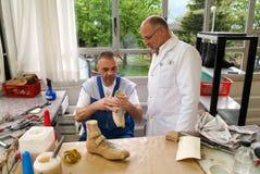 Medico e lavoratore che preparano i sottopiedi ortopedici per un paziente Fotografia Stock