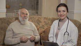 Medico e le vecchie manifestazioni pazienti sfoglia fino alla macchina fotografica stock footage