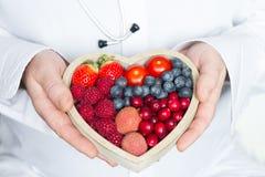 Medico e lo stetoscopio con l'alimento di dieta sana del cuore sottraggono il concetto della medicina immagine stock