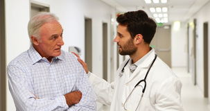 Medico e paziente che discutono sopra la lavagna per appunti nel corridoio archivi video
