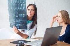 Medico e paziente che esaminano raggi x o concetto di RMI Fotografia Stock