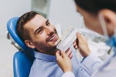 Medico e paziente che scelgono gli impianti del dente fotografia stock