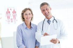 Medico e paziente che sorridono alla macchina fotografica Fotografia Stock