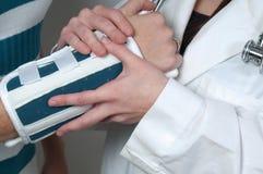 Medico e paziente della donna con il braccio rotto Fotografia Stock