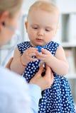 Medico e paziente in ospedale La bambina sta esaminanda dal pediatra con lo stetoscopio Medicina e sanità Fotografia Stock