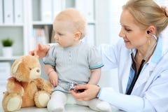 Medico e paziente in ospedale La bambina sta esaminanda dal pediatra con lo stetoscopio Medicina e sanità Fotografie Stock