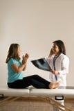 Medico e ragazza soddisfatti dei raggi X Risultato-Verticali Immagini Stock Libere da Diritti