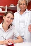 Medico ed assistente che guardano allo spettatore Immagine Stock