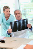 Medico ed infermiera che esaminano i raggi X Fotografia Stock