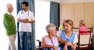 Medico ed infermiere che interagiscono con gli anziani stock footage