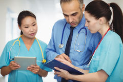 Medico ed infermieri che esaminano lavagna per appunti Fotografia Stock Libera da Diritti