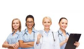 Medico ed infermieri femminili sorridenti con lo stetoscopio Fotografia Stock