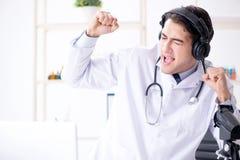 Medico emozionante felice che ascolta la musica durante il pranzo irrompe uff Immagine Stock Libera da Diritti