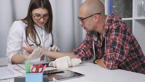 Medico esamina il polso ferito di un uomo paziente archivi video