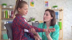 Medico esamina la mano di un adolescente in una sedia a rotelle dopo una fine di lesione su archivi video