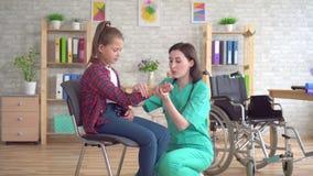 Medico esamina la mano di un adolescente in una sedia a rotelle dopo una lesione video d archivio