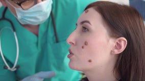 Medico esamina una giovane donna con le grandi talpe sulla sua fine del fronte su stock footage