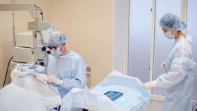 Medico esegue il trattamento dell'occhio, aiuti della cataratta dell'infermiere l'oftalmologo stock footage