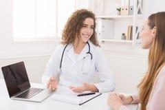 Medico facendo uso del computer portatile e del sistema elettronico di cartella sanitaria immagini stock libere da diritti