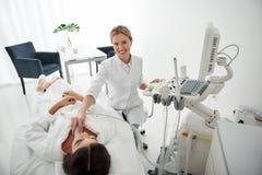 Medico facendo uso dell'analizzatore di ultrasuono e della ghiandola tiroide d'esame di signora fotografia stock libera da diritti