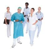 Medico felice in abito chirurgico con i suoi colleghe fotografia stock libera da diritti