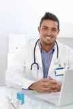 Medico felice che si siede allo scrittorio immagini stock