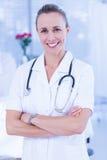 Medico felice che sorride alla macchina fotografica dietro il letto Immagine Stock Libera da Diritti