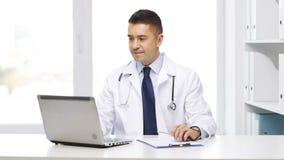 Medico felice con il computer portatile e la lavagna per appunti in ospedale video d archivio