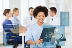 Medico felice con la lavagna per appunti all'ospedale Immagini Stock