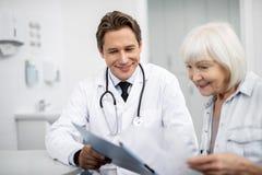 Medico felice e suo il paziente sorridente che esaminano la lavagna per appunti fotografia stock