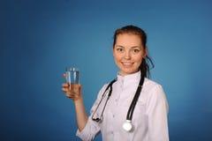 Medico femminile amichevole giovane con bicchiere d'acqua Fotografie Stock