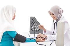 Medico femminile asiatico che controlla pressione sanguigna di un paziente mentre s Fotografia Stock