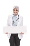 Medico femminile asiatico con lo stetoscopio che tiene bordo bianco in bianco Fotografie Stock Libere da Diritti