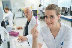 Medico femminile attraente che mostra l'analisi del sangue fotografie stock