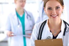 Medico femminile attraente con la cartella davanti a Immagine Stock