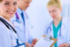 Medico femminile attraente con la cartella davanti a Fotografia Stock Libera da Diritti