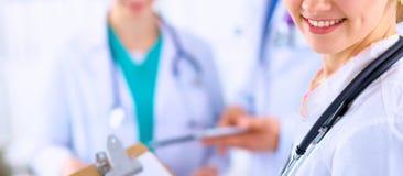 Medico femminile attraente con la cartella davanti al gruppo medico Fotografia Stock Libera da Diritti