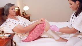 Medico femminile benda la gamba senior della donna a casa stock footage