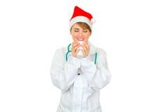 Medico femminile in cappello della Santa che gode della tazza di cof caldo Fotografia Stock Libera da Diritti