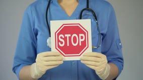 Medico femminile in cappotto blu che avverte circa le malattie serie, tenenti il fanale di arresto video d archivio
