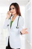 Medico femminile in cappotto del laboratorio con lo stetoscopio che parla dal cellulare Fotografia Stock