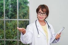 Medico femminile castana che sta con la lavagna per appunti vicino alla finestra immagine stock libera da diritti
