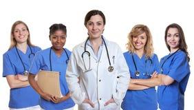 Medico femminile caucasico sorridente con 4 infermieri Immagini Stock